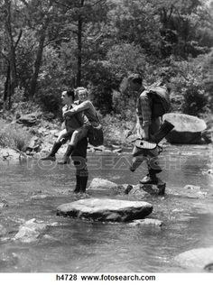 1930S 3 People Crossing Fording Stream One Man Carries Woman Piggy Back Other Carries Angling Fishing Gear Stepping Stones Water View Large Photo Image