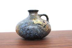 Kleine Vintage Fat Lava Henkelvase aus Keramik vom deutschen Hersteller Ruscha. Die Farbpalette der Vase ist vielseitig und wechselt zwischen scharzm blau und diversen Brauntönen. Die Glasur ist matt.  Die Vase ist in einem sehr guten Vintage Zustand, d.h. keine Risse oder Chips.  Hersteller: Ruscha Keramik | West Germany  Gemarkt: 301-1 Maße: Höhe: 12 cm | 4.72 inch Durchmesser Öffnung: 5 cm | 1.96 inch Gewicht: 578 g  Der Versand erfolgt aus Deutschland! Kombiversand möglich. Bitte…