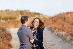 red haired woman wearing a black dress with white flowers and green earrings and a masculine coat with red nail varnish smiling at her future husband wearing a checkered shirt for an engagement shoot<br> Dusty Pink Weddings, Dusty Rose Wedding, Red Nail Varnish, Fall Wedding Drinks, Polaroid Wedding, Ireland Beach, World Trends, Green Earrings, Engagement Shoots
