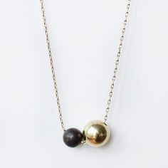 "Another Feather - Solid brass sphere hung beside a smaller oxidized black brass one on a 28"" brass chain, this piece has such a nice weight to it."