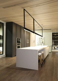 Gorgeous streamlined kitchen. Strong monolithic white kitchen island and lovely linear light feature. I'd like the dark cabinets By Gibeault Design Inc.| Design - Cuisine - Intérieur
