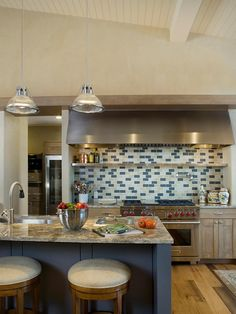 A subtle dose of blue adds just the right amount of vintage-inspired charm to this contemporary kitchen. The most noticeable design element is the scattered blue-and-ivory tile backsplash above the stove. The sporadic tile placement makes the backsplash the focal point and ties the entire color scheme together. Image courtesy of Slifer Designs