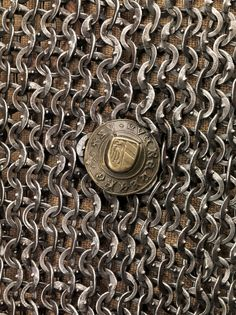 European (German) riveted mail hauberk, with makers mark, detail view, 15th century, steel, latten Dimensions: H. (as mounted) 36 in. (91.5 cm); Wt. 20 lb. (9071.9 g), Met Museum.