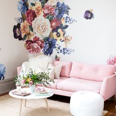 A variety of vintage styled floral wall decals in many different shades of violet, orange, purple, white, and pink. Each wall decal has vibrant colors and full graphic detail. The decals are placed on a white wall behind a pink couch and white coffee table in a living room.