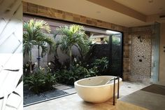 Garden Bath - A wall of bi-fold doors open to bring the outdoors inside the master bath.