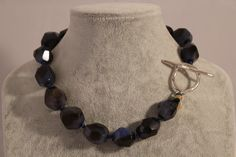 This necklace is crafted with organic shapes, natural stones, and exuberant blue hues.  Agates knotted with silk in between with silver clasp.