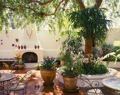 Lush Spanish style patio with saltillo tile floor and stucco fireplace