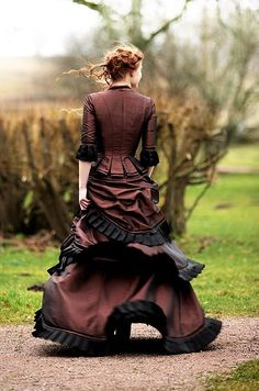 This is an Victorian Bustle dress. You can tell by the drapes flowing down at the back of the skirt and the fitted bodice of the princess lined jacket. I love the inverted box pleats that follows the seam lines and the black trimmings compliments the colour of the dress.