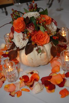 fresh white pumpkin with berries and fall shade roses and petals on table top