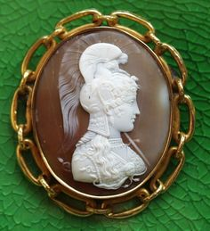 Athena - Minerva      Materials: shell, gold (UNmarked)  Size of the cameo: 2 1/16 x 1 3/4  Size of the frame: 2 5/8 x 2 5/16  Date and origin: Italy, ca 1820-30.  The frame is likely English, probably made around 1880.  Condition: several hairlines on the background. Several dents on the frame. The figure is mint, without wears