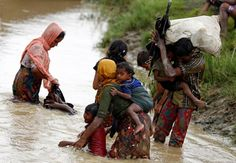 Rohingya refugees wash mud from their clothes while crossing a canal in Teknaf, Bangladesh. REUTERS/Mohammad Ponir Hossain