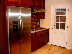 Shaker Heights OH Kitchen Remodel: Karftmaid Cherry cabinets, granite, The Tile Shop Sandlewood travertine tile flooring, Copper Rust slate floor insets & backsplash, GE stainless steel appliances