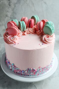 Pink baby shower cake topped with macarons and sprinkles