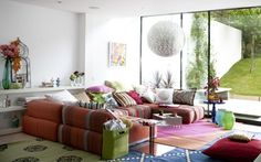 un canapé grand à rayures et des coussins bariolés dans la salle de séjour