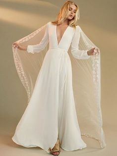We don't recommend getting married just because you've fallen in love with the perfect wedding dress. But who are we to judge? This is a floor length, wrap dress with long sleeves and a deep v neckline.