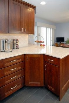 A light cherry color makes the white of the granite countertops really pop. With a bolder frame for the doors it also creates a more rustic style.