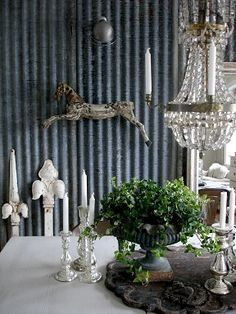Love the mix of chic and rustic: silver, chandeliers, iron urn sheet metal walls.