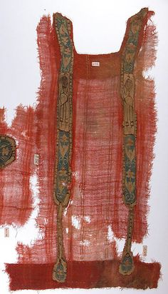 6th–9th century Egypt  Coptic tunic fragment is accented with stitching and undyed linen self-bands (ornamental bands of multiple, undyed weft threads). The decorative clavi in gold, brown, and blue tones were woven separately and applied. Each combines the figure of a female, a saint, with panels of gold palmettes on a blue ground; a gold pendant decorated with a leaf dangles from each. Textual and visual sources attest to the existence of tunics of different weights, which could be layered