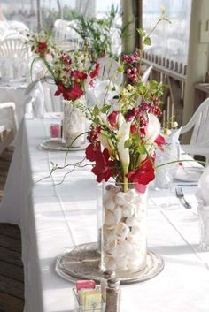 Hawaiian centerpiece - white shells in tall vases with bright burgundy red flowers mixed with white