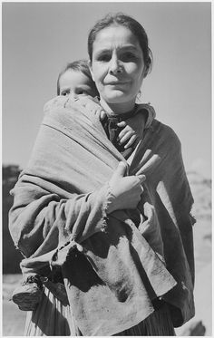 "Original Caption: ""Navajo Woman and Child, Canyon de Chelle, Arizona."" [Canyon de Chelly National Monument] (vertical orientation) U.S. National Archives' Local Identifier: 79-AA-K05 From: Series: Ansel Adams Photographs of National Parks and Monuments, compiled 1941 - 1942, documenting the period ca. 1933 – 1942 Created By: Department of the Interior. National Park Service"