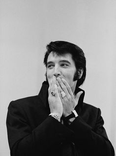 Wearing two of his trademark rings... Elvis designed much of his own jewelry with the help of Lowell Hayes, his personal jeweler.