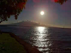 The sun hangs over the Island of #Lanai. Photo taken from the shores of Lahaina #Maui. #Hawaii #travel #gohawaii