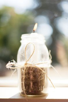 Mason jar with sand & a taper candle, twine tied around the jar