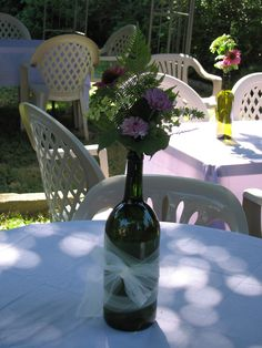 Liz's Bridal Shower- centerpieces: tinted wine bottles wrapped in tulle, and filled with wildflowers