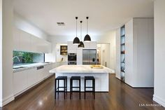 Gorgeous contemporary kitchen.  White cabinetry, marble bench tops, black pendants and stools. #kitchendesign