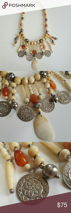 """Stone and Bone Necklace This amazing and unique large detailed necklace is made of carved bone beads and charms with natural cut and polished orage red Agate stone with 925 Sterling Silver coin flower sun stamped charms. This is very colorful and heavy vintage piece of jewlery. Each bead is approximately 1cm the dangling pieces hang down 3"""" and the center piece is 4"""" long the nwcklace chain is 21"""" long. This is a lovely accessory great with your favorite outfit. Other great accessories in my…"""