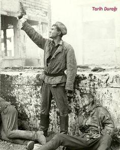 A Red Army Soldier standing next to dead German soldiers while getting ready to shoot a flare, Stalingrad.    Stalingrad was one of the most bloody war in the history and World War 2