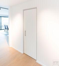Moderne witte binnendeur met een aluminium blokkader en een ingebouwde handgreep. Anyway binnendeuren kenmerken zich door de aanpasbare draairichting en scharnierzijde, de onzichtbare scharnieren met automatische sluithulp en ingebouwde ventilatietechnieken. De gebruikte hightech materialen zijn onderhoudsvriendelijk, schildervrij en krasbestendig. Deze volledig afgewerkt deur kost ongeveer 825.00 euro excl. BTW.