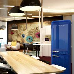 """Offene """"Wohnzimmer-Esszimmer-Küchen-Kombination"""" mit blauem SMEG Kühlschrank als Farbtupfer."""