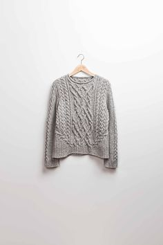 """To give the basic Aran pullover a little pizzazz, I added the bias cables on the front and back pieces. They add interest not only by changing the flow of the cables, but by changing the entire silhouette of the sweater. The biasing gives the slightest hint of a peplum and accentuates the waist naturally. And to keep the femininity, the neckband is a soft rollover versus a traditional ribbed neckband."" – Michele Wang"