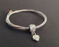 A handmade recycled guitar string bracelet/bangle with a silver coloured charm. Beaded Bracelet Patterns, Beaded Jewelry, Handmade Jewelry, Handmade Silver, Diy Jewelry, Guitar String Bracelet, String Bracelets, Cute Bracelets, Bangle Bracelets