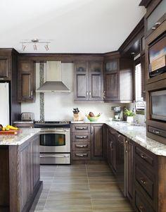 Armoires de cuisine de style classique. L'îlot et la totalité de la cuisine ont été réalisé en merisier. Le tout est harmonisé avec un comptoir de granit.