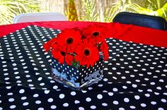 Red tablecloth, polka dot square in the middle, square vase with black and white polka dot ribbon wrapped around the middle, black and white florist gel beads and red daisies. The perfect centerpiece for a ladybug themed party.