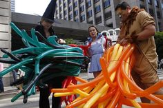 Julie Anderson (left) Didi MacDonald, and Omar Hernandez untie their balloons to complete their costumes for the Parkmerced Float in the San Francisco Pride Celebration and Parade on Sunday. Photo: Audrey Whitmeyer-Weathers, The Chronicle
