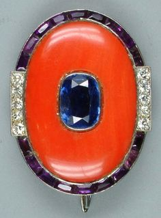 An Art Deco coral, sapphire and amethyst brooch, by Cartier, circa 1925. The oval coral plaque set to the centre with a collet mounted mixed-cut sapphire, within a border of amethyst and single-cut diamonds, signed Cartier, Paris, Londres, New York, numbered, with French assay marks, coral plaque later replacement. #Cartier #ArtDeco #brooch