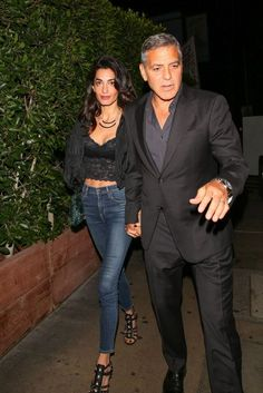 Amal Clooney stepped out for a night with her hubby George Clooney wearing yet another amazing street style outfit. Date night inspiration? Yes! She looked stunning in a cropped black lace camisole with high-waisted jeans, a black bomber jacket, a layered necklace and strappy heeled sandals.