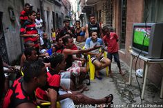 Flamego fans watch soccer game on TV in a Favela da Mare alley. Rio de Janeiro, Brazil.  Flamengo is the most popular team in Brazil and one...