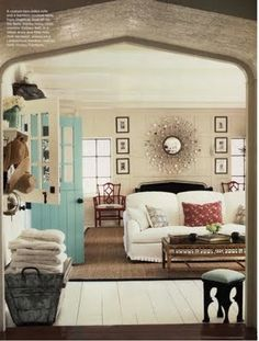 This living room can be classified as an accented-neutral color scheme. The neutral colored couch, rug, and walls are accented by the light blue door and red pillow.