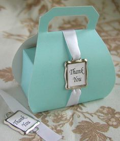 """Our unique """"Thank You"""" Purse Favor Box Kits are an adorable way to show your gratitude to each of your guests.  Just choose your box color, choose your ribbon color, and you'll be sent nearly everything you need to create beautiful favor boxes.  Each box arrives with our classic metal-framed """"Thank You"""" tag.  Priced per set of 10 kits"""
