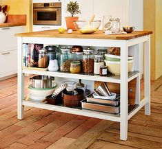 White IKEA kitchen island with a solid wood worktop. Two shelves underneath for storage.