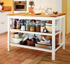 Isla de cocina de IKEA con encimera de madera maciza. Dos estantes debajo.