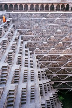 Chand Baori Temple and Stepwell,India. The woman in the orange Sari is sweeping the dust downward,step by step,in the scorching sun. India Architecture, Ancient Architecture, Amazing Architecture, Architecture Details, Landscape Architecture, Luigi Snozzi, Stairway To Heaven, Incredible India, Stairways