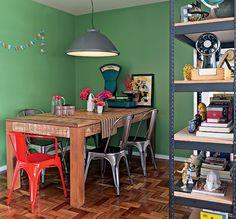 A sala de jantar ganhou paredes verdes, que contrastam com a poltrona Model A, de Xavier Pauchard, vermelha. Projeto da designer de interiores Renata Parasmo