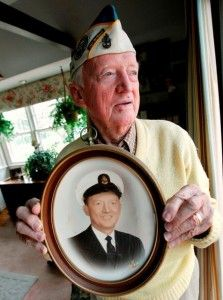 An elderly Pearl Harbor veteran holds an old photo of his younger self in service.