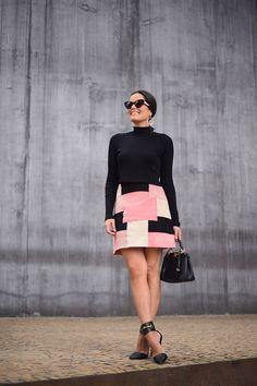 Mariah Bernardes de blusa gola alta preta e saia de estampa geométrica rosa, nude e preta