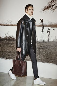 A look from the #CoachMens2015 presentation: the Black Leather Fireman Coat, White/Black Chunky Rib Rollneck with Tipping, Black Wool Trousers, Feather Necklace, Black Cord Key, Lo-Top and Mahogany Pebbled Small Manhattan Tote